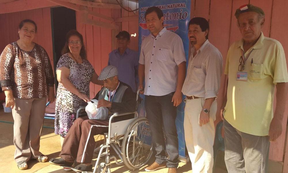 Teófilo Céspedes recibiendo su silla de ruedas por parte de representantes de Agua Mineral San Antonio //OviedoPress