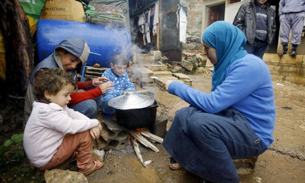 Mujer refugiada siria con sus hijos prepara comida cerca de su tienda. //arabia.watch
