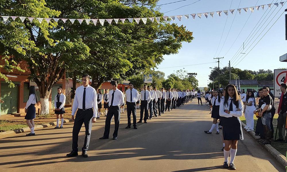 Desfile estudiantil sobre la avenida principal de la ciudad.