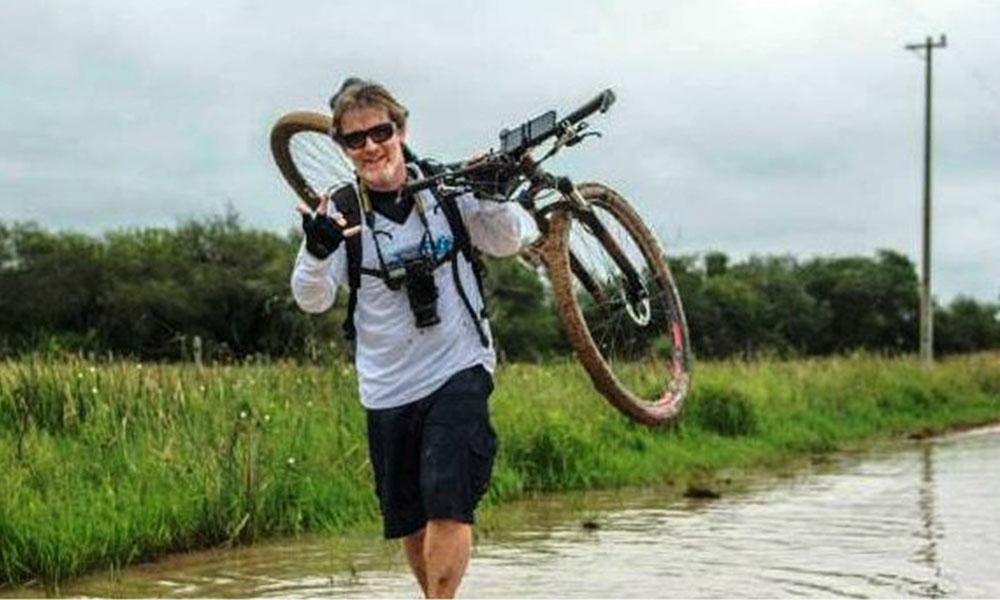 El joven atraviesa por tramos difíciles con una bicicleta.